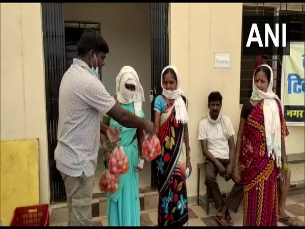 A village official hands out tomatoes to people lining up to get vaccinated. (Photo/ANI)