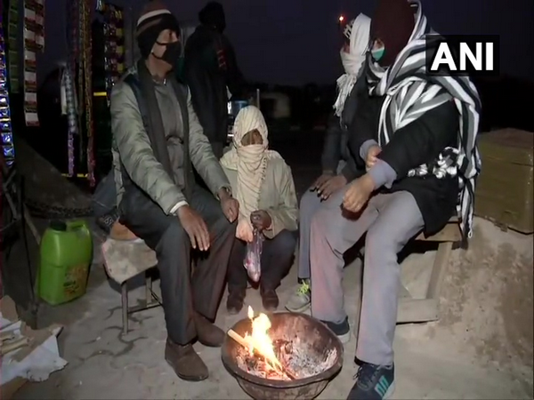 People were seen sitting near the fire on Sunday in Delhi's Anand Vihar area. (Photo/ANI)