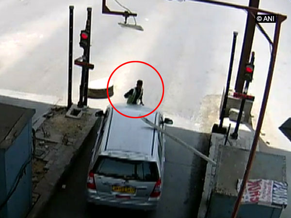 A video grab of CCTV footage of the car which drives away with toll plaza employee on car's bonnet. (Photo/ ANI)