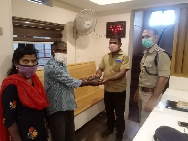 Police officials handing over the wallet to its owner.