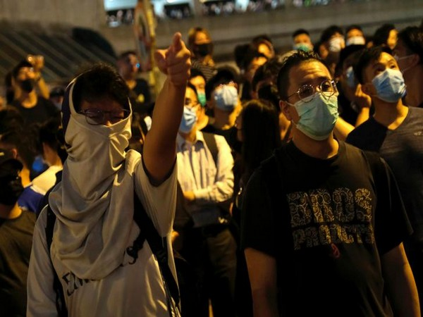 Protesters shouting slogans while clashing with police forces in Hong Kong on Tuesday night.
