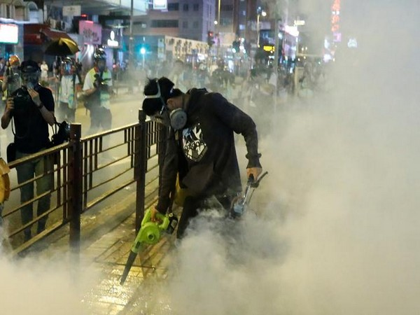 A protester uses a leaf blower to disperse tear gas during an anti-government demonstration in Hong Kong on Sunday