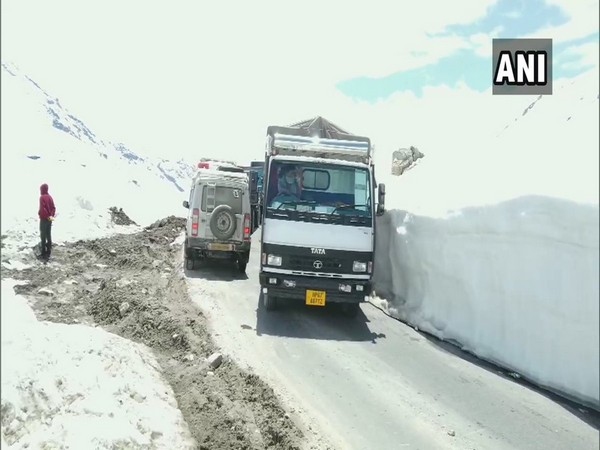 Truck drivers drive through snow-clad Rohtang Pass to deliver essential goods in Himachal Pradesh on Wednesday. Photo/ANI