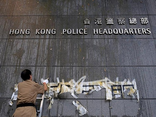 A staff tries to clean off the marks from thrown eggs and anti-extradition graffiti on the walls of the Hong Kong Police headquarters here on Saturday