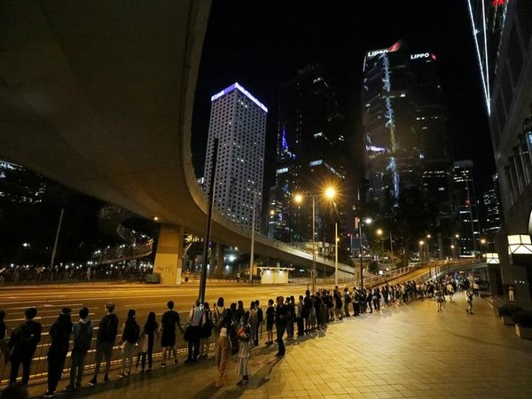 Protesters hold hands to form a human chain during a rally to call for political reforms in Hong Kong on Friday night