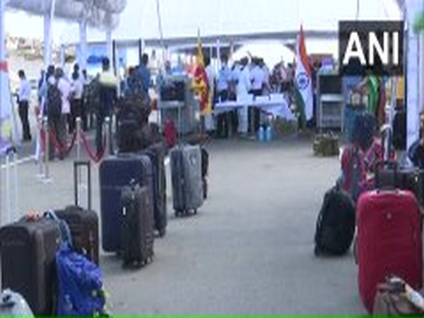 Indian nationals wait to board INS Jalashwa at Colombo on Monday.