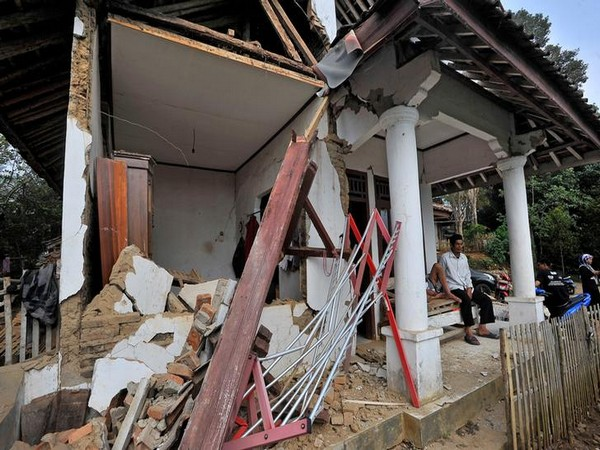 Locals sit at their house damaged after an earthquake hit in Pandeglang, Banten province, Indonesia, on Saturday