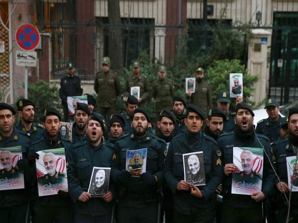 Iranian policemen hold pictures of the late Iranian Major-General Qassem Soleimani, during a protest against the assassination of Soleimani, who was killed in an airstrike at Baghdad airport.