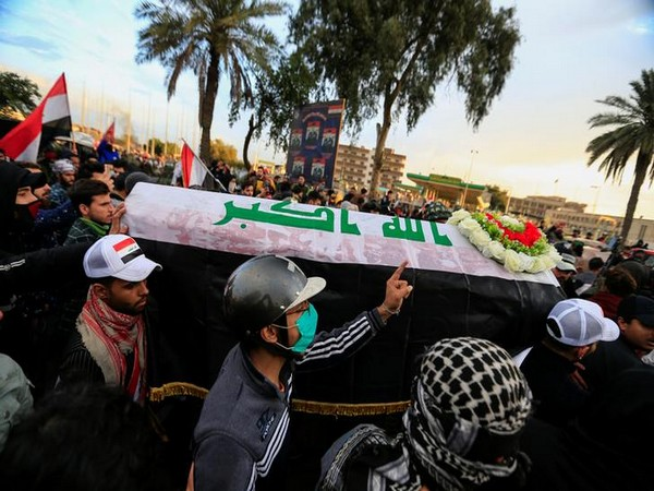 Mourners carry a mock coffin for an Iraqi demonstrator, who was killed on Tuesday during ongoing anti-government protests in Baghdad, Iraq