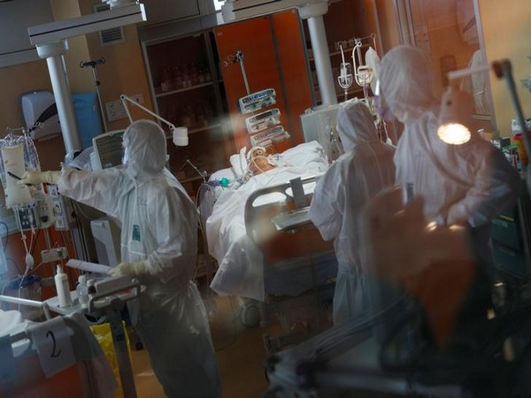 Medical workers in protective suits treat patient suffering from coronavirus in ICU at a hospital in Rome dedicated to treating COVID-19.