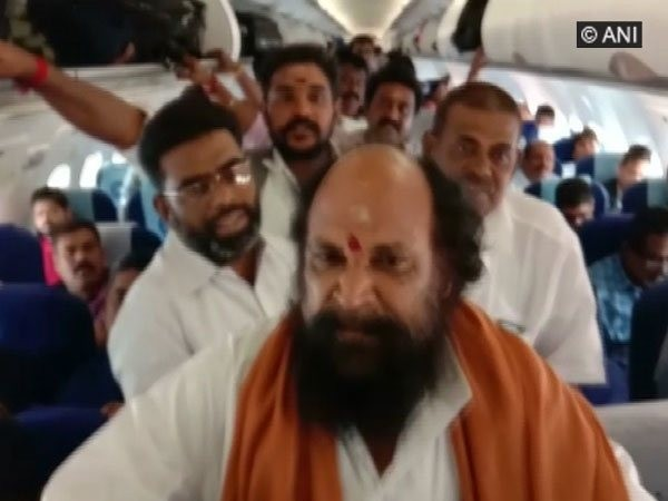 K A Murugan and his supporters raise slogans inside the flight heading to Madurai on Saturday.