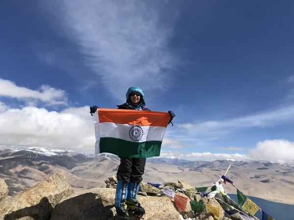 Kaamya Karthikeyan holding an Indian flag at the top of Ladakh's Mt Mentok Kangri II