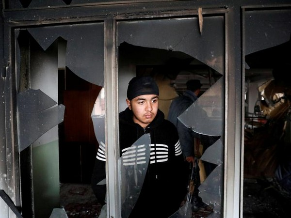 An Afghan Sikh inspects a damaged window inside the gurdwara complex after the attack in Kabul