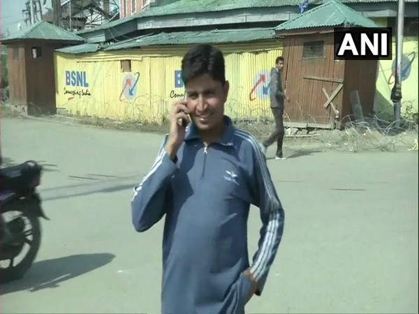 A local in Srinagar talking on the phone after postpaid mobile services were restored in Jammu and Kashmir on Monday.