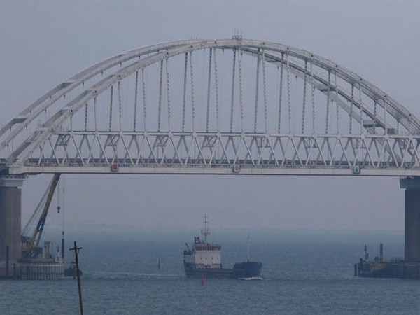 A vessel sails under a bridge connecting the Russian mainland with the Crimean Peninsula across the Kerch Strait