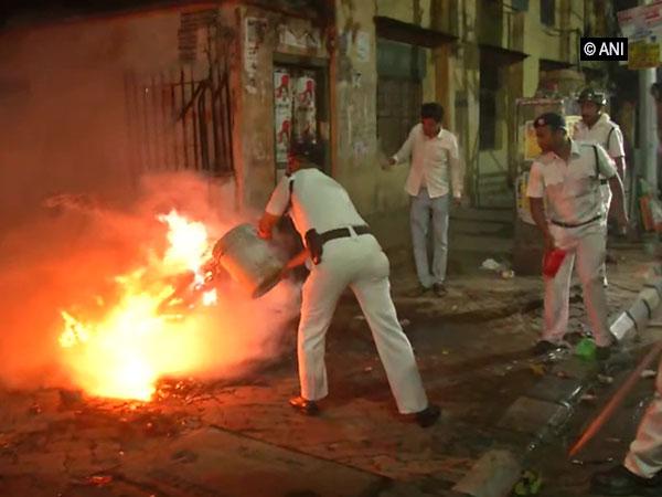 Policemen dousing a blaze following clashes during Amit Shah's roadshow in Kolkata on Tuesday. (Photo/ANI)