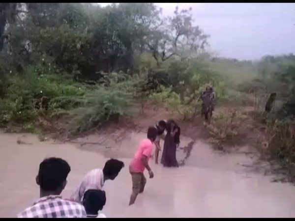 Locals rescuing girl, her grandmother in Karnataka's Koppal district on Sunday. (ANI/Photo)