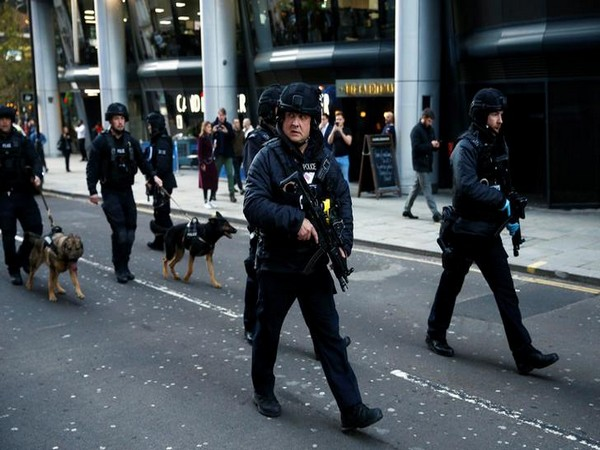 Police with sniffer dogs search the area where the stabbing took place at London Bridge on Friday.