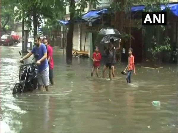 People negotiate knee-deep water in Mumbai