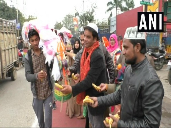 Some Muslims offering fruit to a Kanwar yatri in Aligarh on Sunday.
