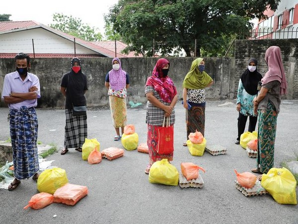 Rohingya refugees wearing protective masks wait for receiving goods from volunteers in Kuala Lumpur