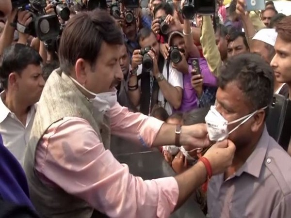 Delhi BJP president Manoj Tiwari distributing masks on Sunday in New Delhi. Photo/ANI
