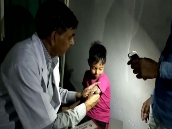 Visual of a doctor treating a child in flashlight at UP hospital. Photo/ANI