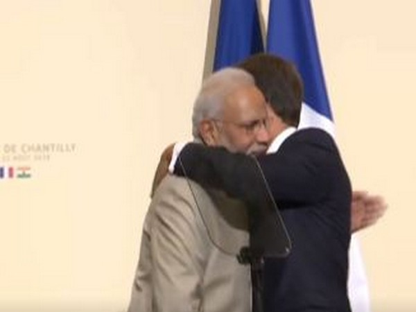 French President Emmanuel Macron and Prime Minister Narendra Modi pat each other during a joint interaction in Chantilly on Thursday