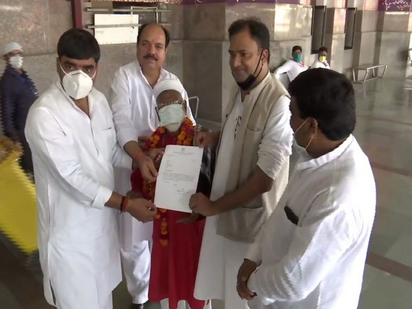 Congress workers present appreciation letter to 80-year-old Mujibullah for his extraordinary service at Charbagh Railway Station in Uttar Pradesh on Saturday. Photo/ANI