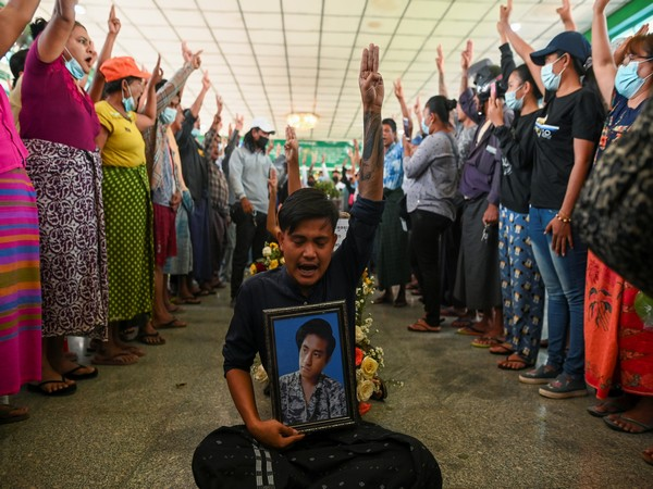 Myanmar citizens flashing a three-finger salute as they hold funeral of one of the victims of military security forces. (Photo credit: Reuters)