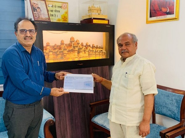 NAFED Managing Director Sanjeev Kumar Chadha handing over cheque to Union Agriculture Minister Narendra Singh Tomar. (photo/ANI)