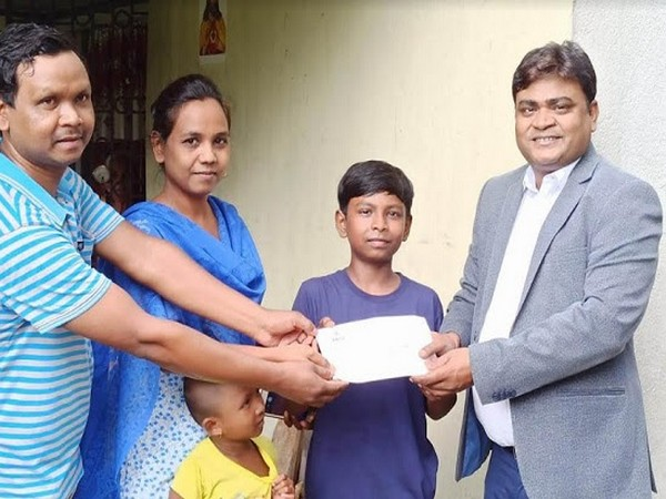 Mr. Ujjwal Sinha - Divisional Manager, Sany Heavy Industry India Pvt. Ltd. presenting the Demand draft to Joy Anugrah Kerketta, son of Mr..Kuldip Kerketta standing along with his wife and daughter.