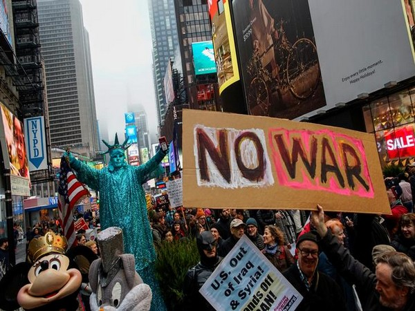 People march as they take part in an anti-war protest amid increased tensions between US and Iran at Times Square in New York.