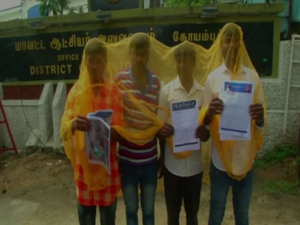Protesters wearing mosquito net outside the District Collector's office in Coimbatore on Tuesday.