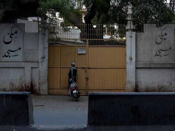 A man stands at the closed entrance of the Makki Masjid Tablighi center, after the government ordered to quarantine the center in Karachi