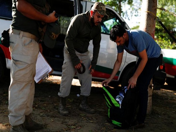 Mexican migration officers inspect the belongings of a Pakistani migrant after he was detained for not providing documentation in October 2018.