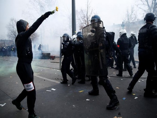 A protestor clashes with police during protest against planned pension reform in Paris on Thursday.