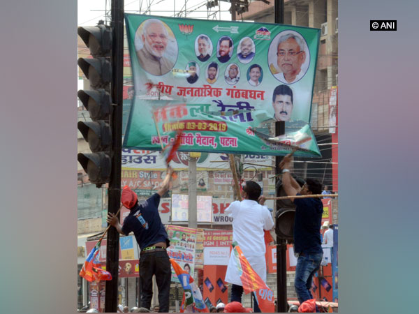 Quota supporters removing the banner of BJP-JDU in Patna on Tuesday. Photo/ANI