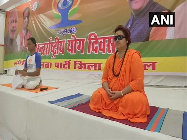 BJP leader Pragya Singh Thakur performs yoga at the party office in Bhopal on International Yoga Day on Sunday. [Photo/ANI]