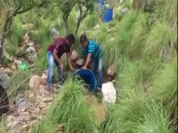 Officers of Excise and Special Enforcement Bureau police destroying country liquor in Kakarla forest area (Photo/ANI)