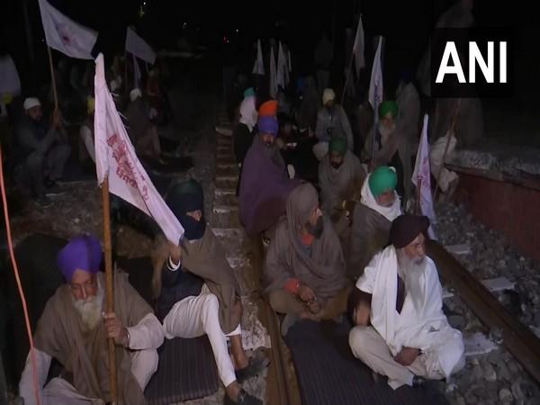 Kisan Mazdoor Sangharsh Committee members block railway tracks in Amritsar's Jandiala Guru on Monday night to protest against the recently enacted farm laws. (Photo/ANI)