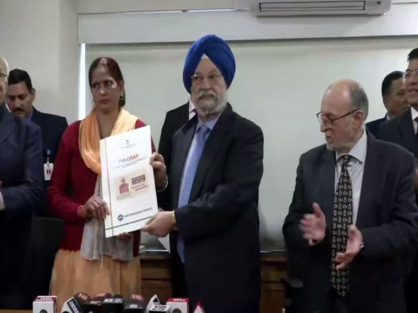 Union Minister Hardeep Singh Puri handing over the registry papers to the first beneficiary under PM-UDAY in New Delhi on Friday. Photo/ANI
