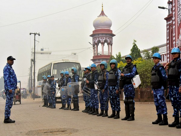 Security personnel stand guard near the Aligarh Muslim University during the protest against Citizenship Amendment Act, 2019, in Aligarh on Saturday.