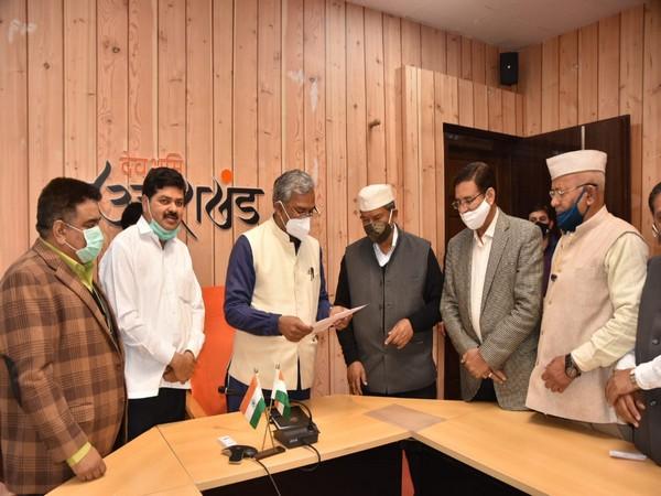 Visual of former Uttarakhand CM Harish Rawat meeting Trivendra Singh Rawat (Photo/ANI)