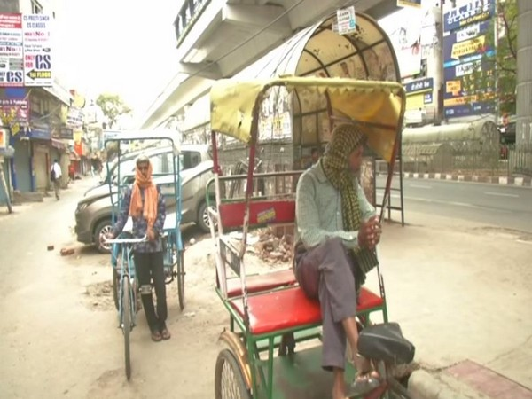 Two rickshaw pullers wait for customers amid lockdown in the national capital. Photo/ANI