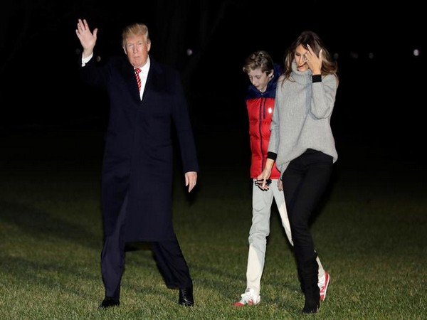 U.S. President Donald Trump waves as he walk with First Lady Melania Trump and their son Barron on the South Lawn of the White House