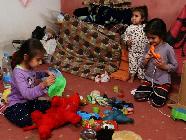 Syrian refugee kids play with toys inside a room at a makeshift Syrian refugee camp in the Lebanese border town of Arsal, Lebanon