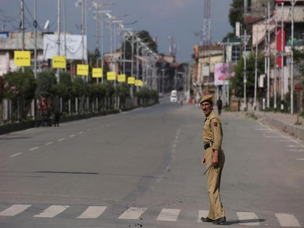 A policeman crosses an empty road during restrictions in Kashmir on Monday. Photo/Reuters