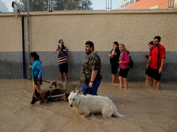 People wade through a flooded street as torrential rains hit Orihuela, Spain on September 13
