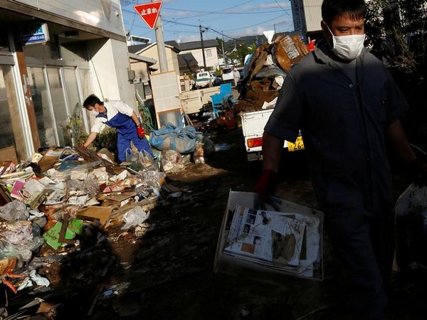 Locals clean a house, in the aftermath of Typhoon Hagibis, in Yanagawamachi district in Japan. Photo/ANI